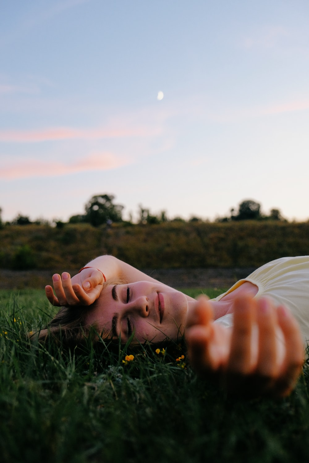 woman in white shirt lying on green grass field during daytime