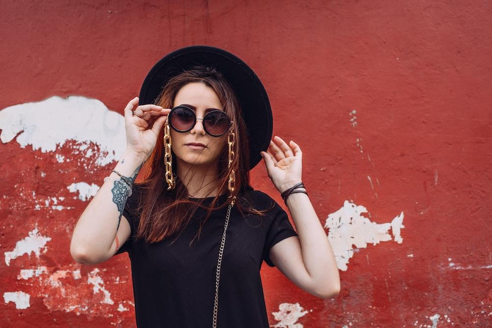 woman in black tank top wearing black sun hat and sunglasses