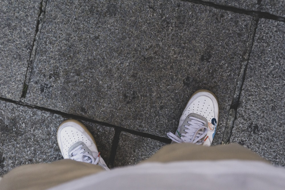 person wearing white converse all star high top sneakers