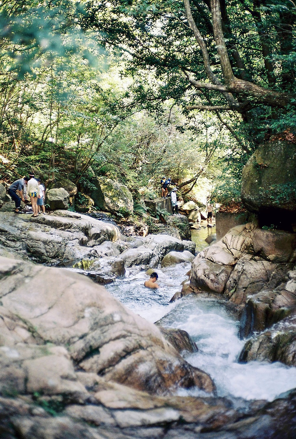 people walking on rocky river during daytime