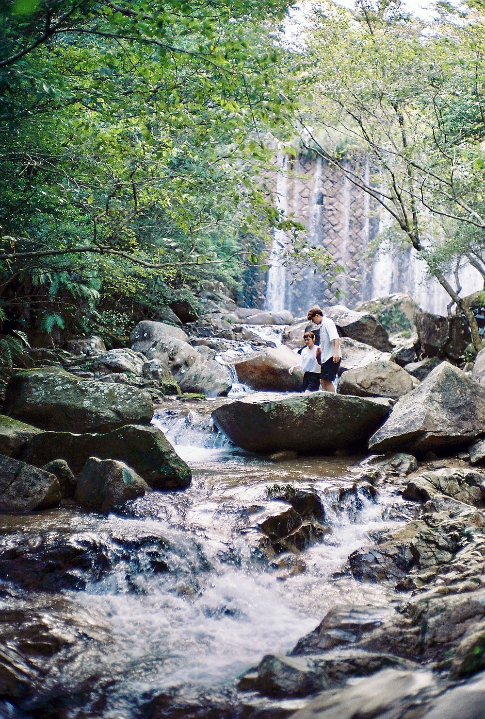 woman in white shirt sitting on rock in river during daytime