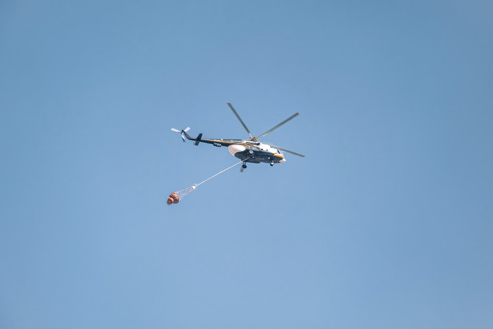 white and black helicopter in mid air