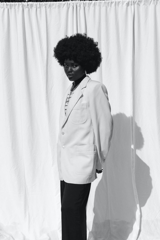 woman in white blazer standing near white curtain