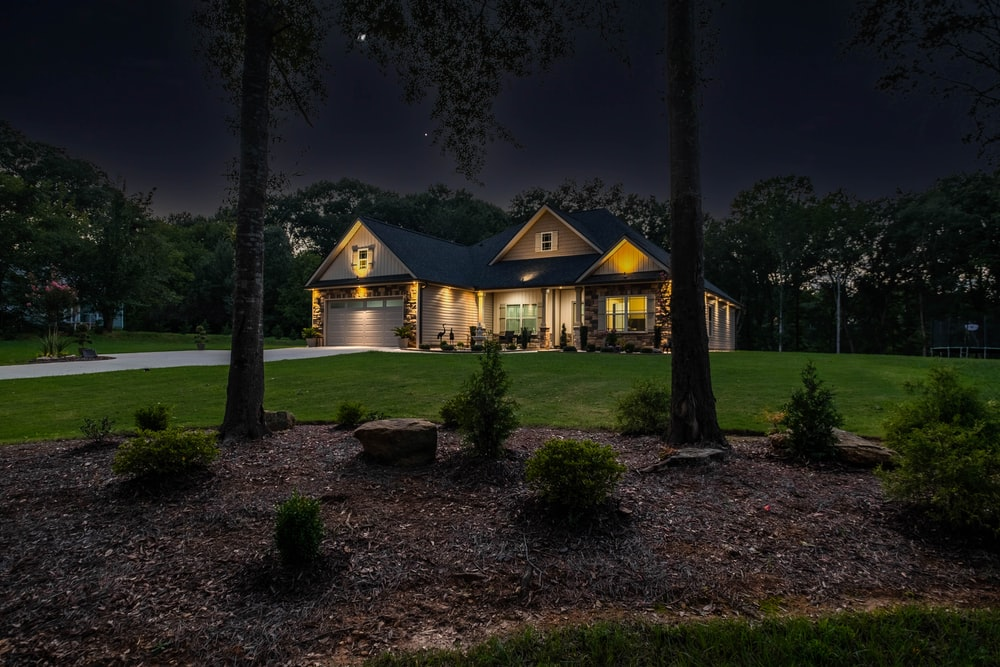 brown wooden house surrounded by trees during nighttime