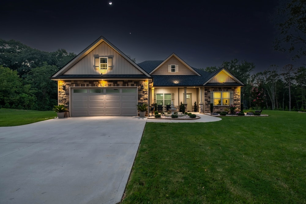 brown wooden house near green grass field during night time