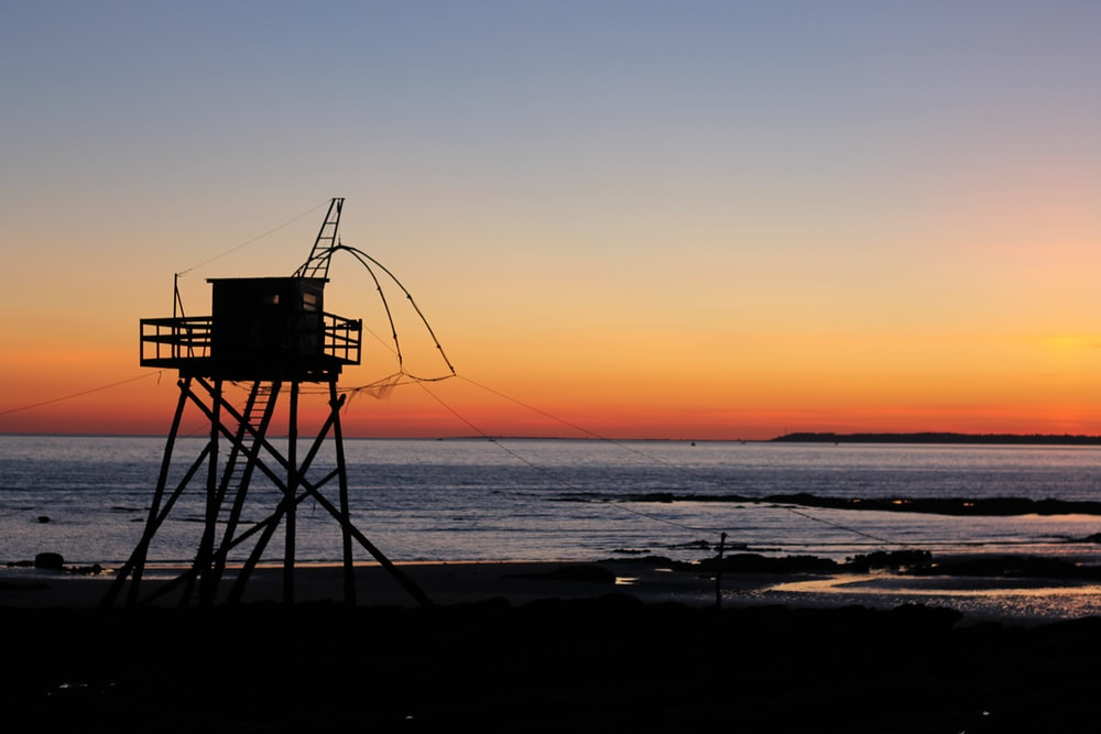 silhouette of lifeguard tower on beach during sunset