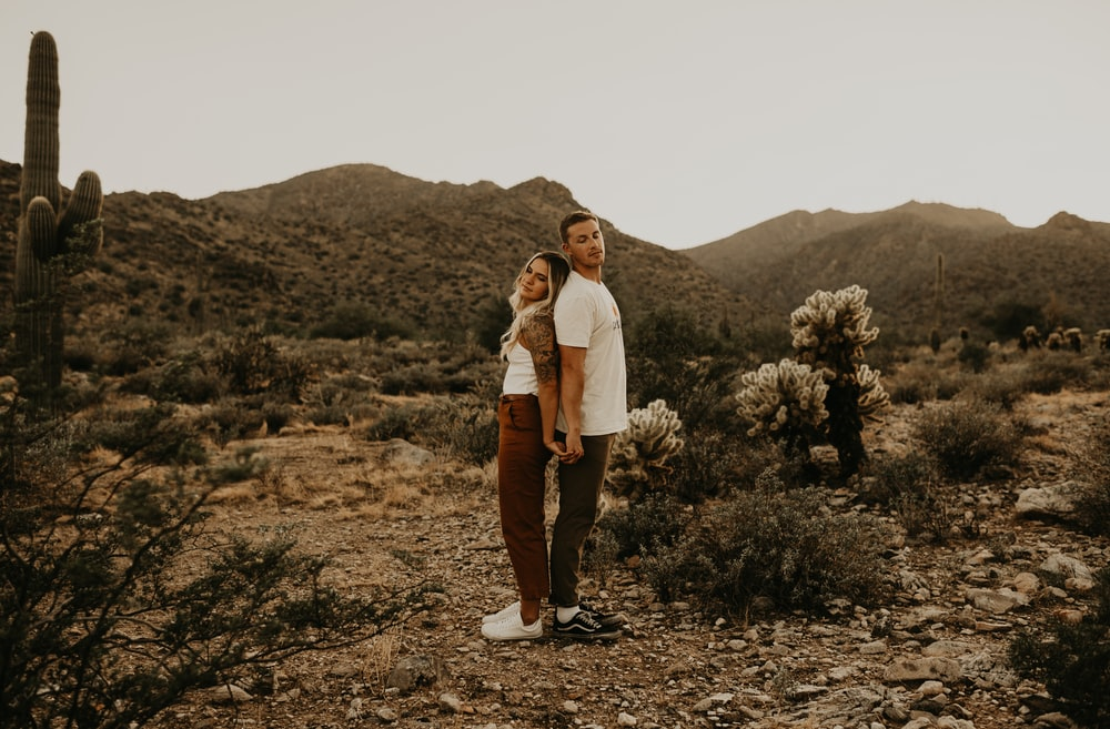man and woman standing on brown dirt ground during daytime