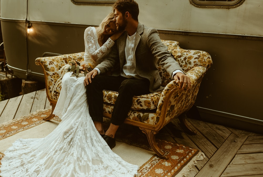 woman in white wedding gown sitting on brown wooden armchair