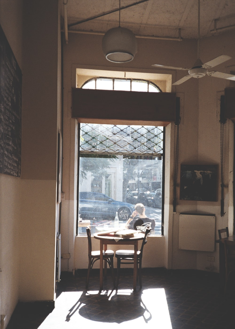 brown wooden table and chairs near window