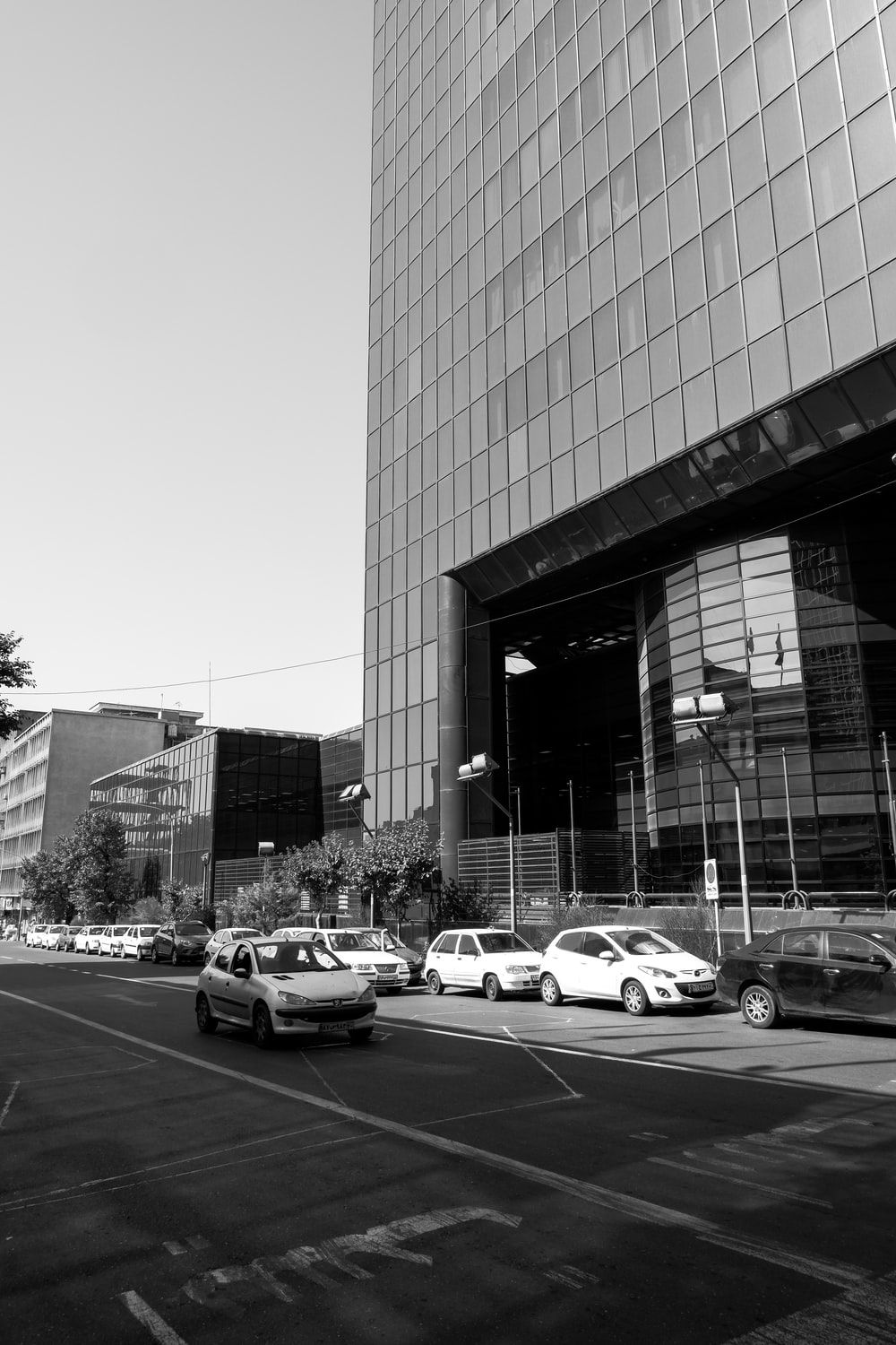 grayscale photo of cars parked near building