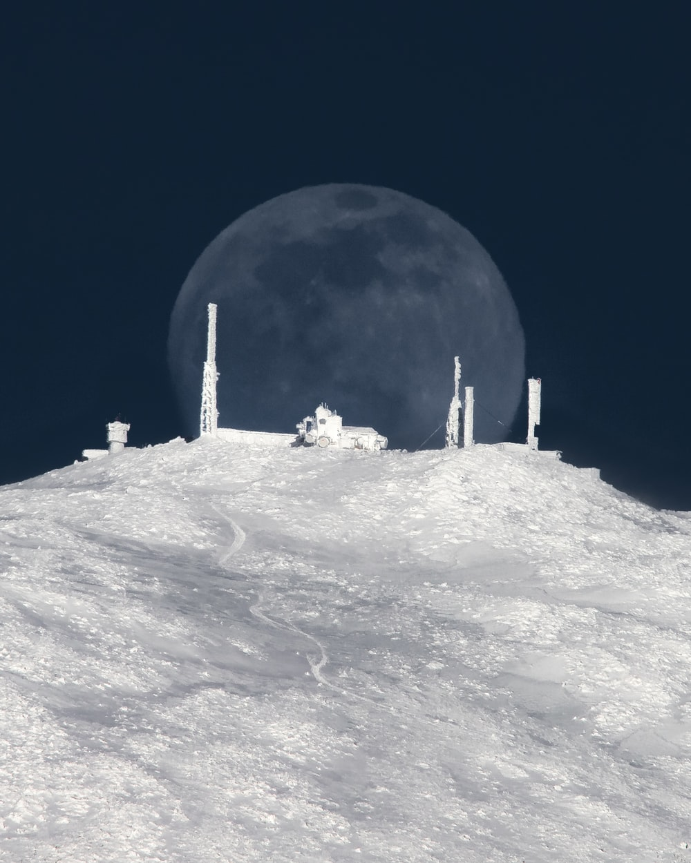 white and gray building on white snow covered mountain during night time