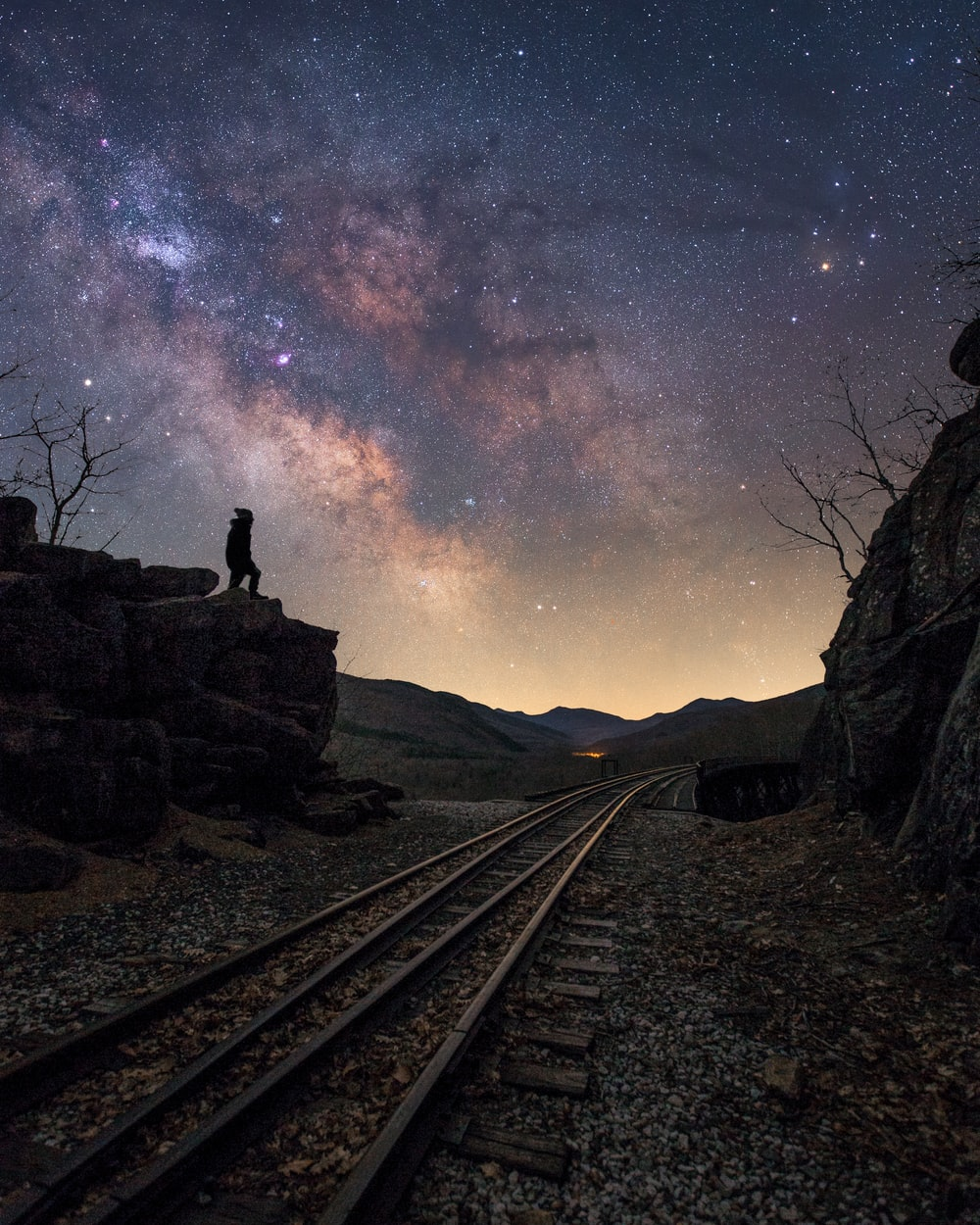 man standing on train rail during night time