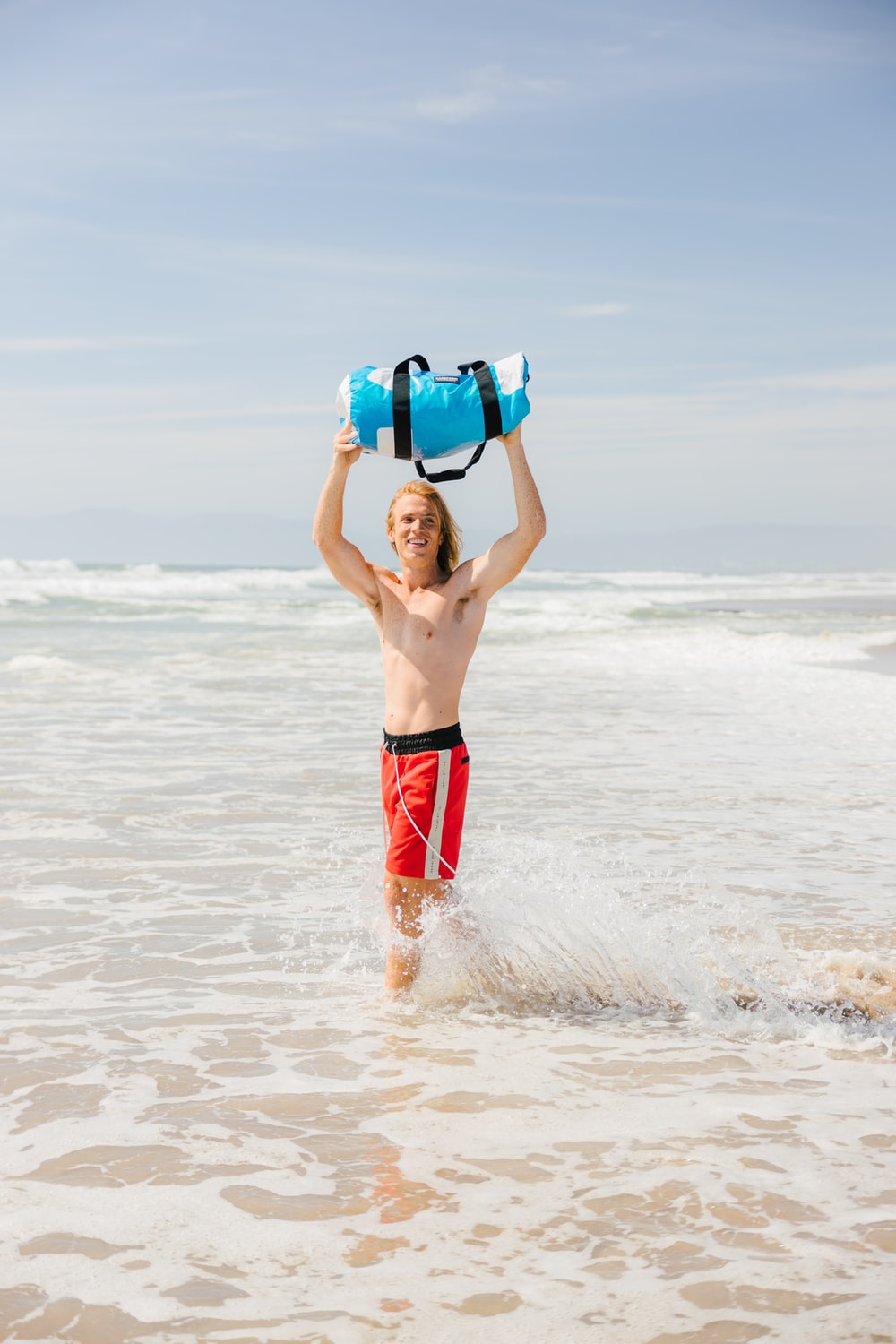 man in blue and red shorts on beach during daytime