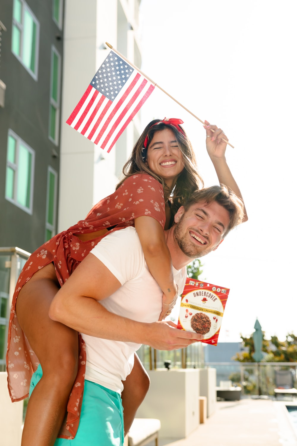 2 women smiling and standing near white and red flag during daytime