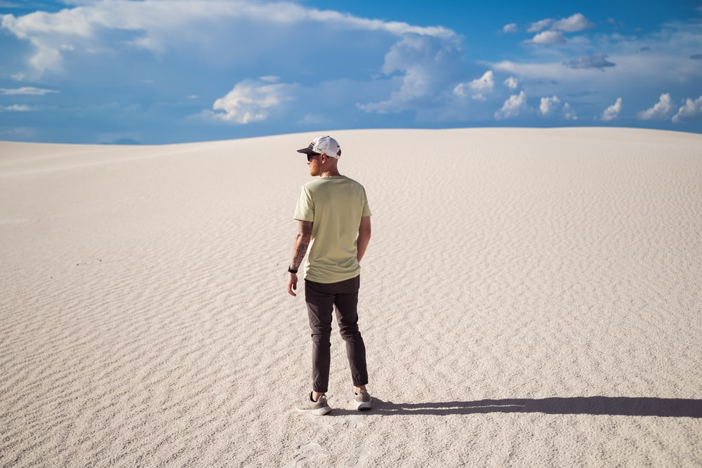 man in green shirt and blue denim jeans standing on white sand during daytime