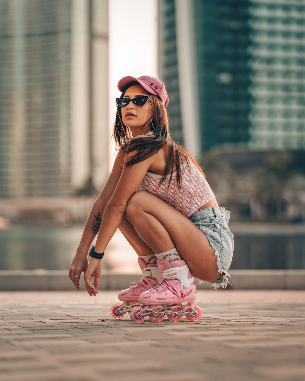 woman in blue denim shorts and red floral shoes sitting on concrete floor during daytime