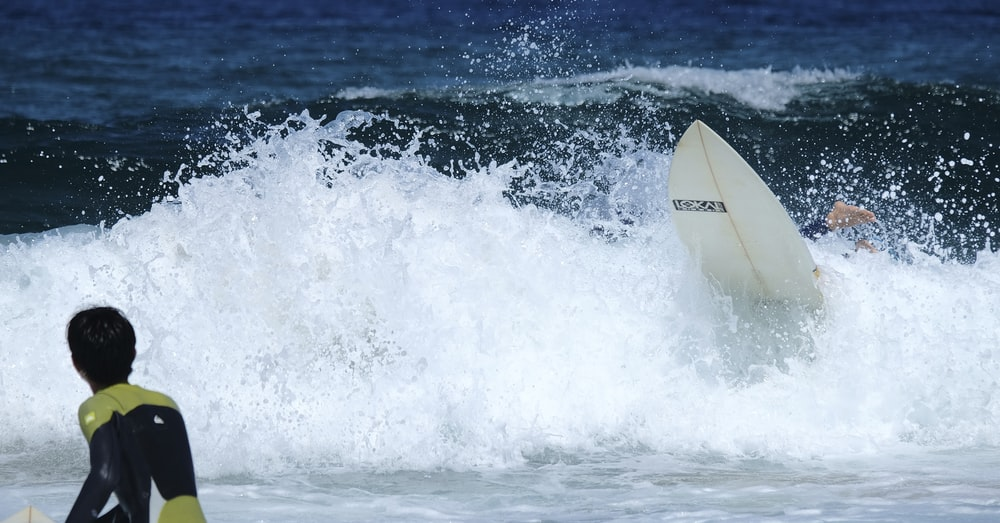 white surfboard on body of water during daytime