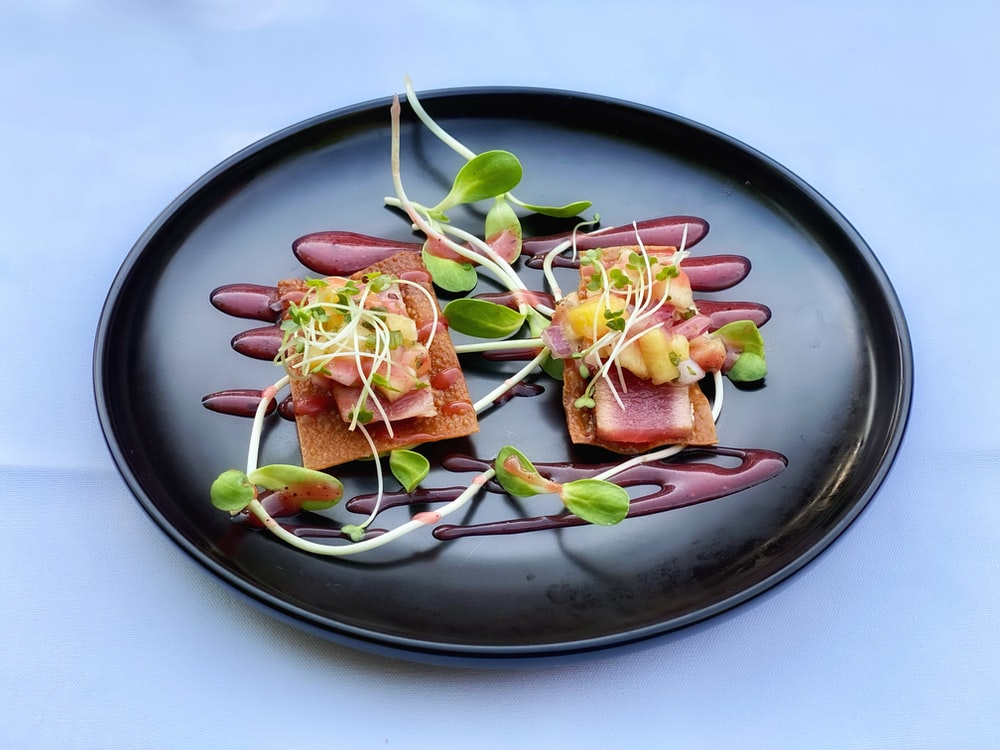 sliced meat with vegetable on black round plate