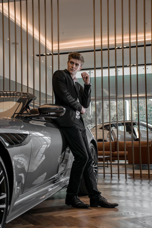 man in black suit standing beside silver car