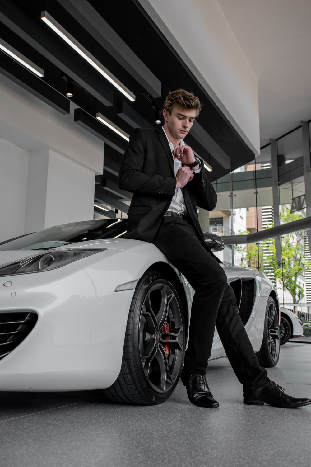 man in black suit standing beside white car