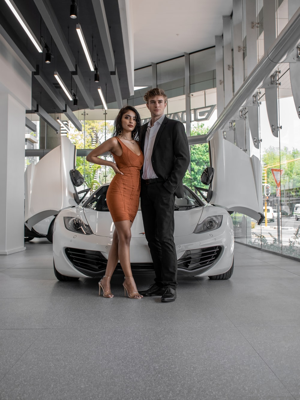woman in black sleeveless dress standing beside white car