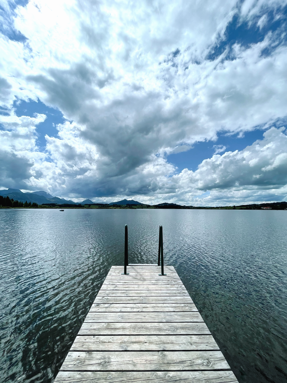 brown wooden dock on body of water under blue and white cloudy sky during daytime
