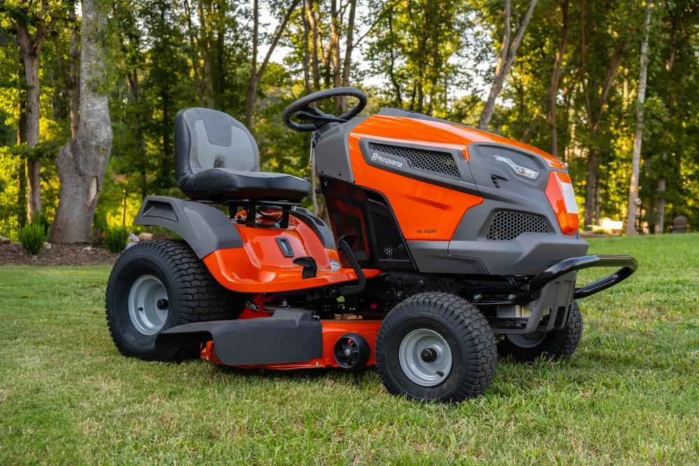 orange and black ride on lawn mower on green grass field