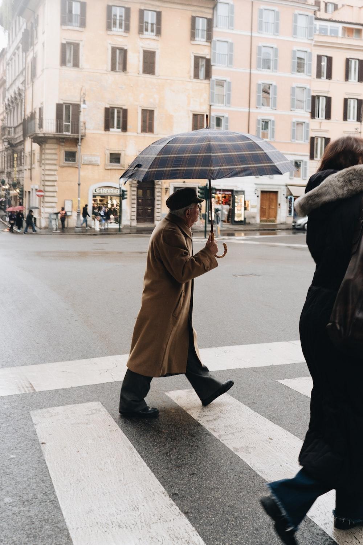 woman in brown coat holding umbrella walking on sidewalk during daytime