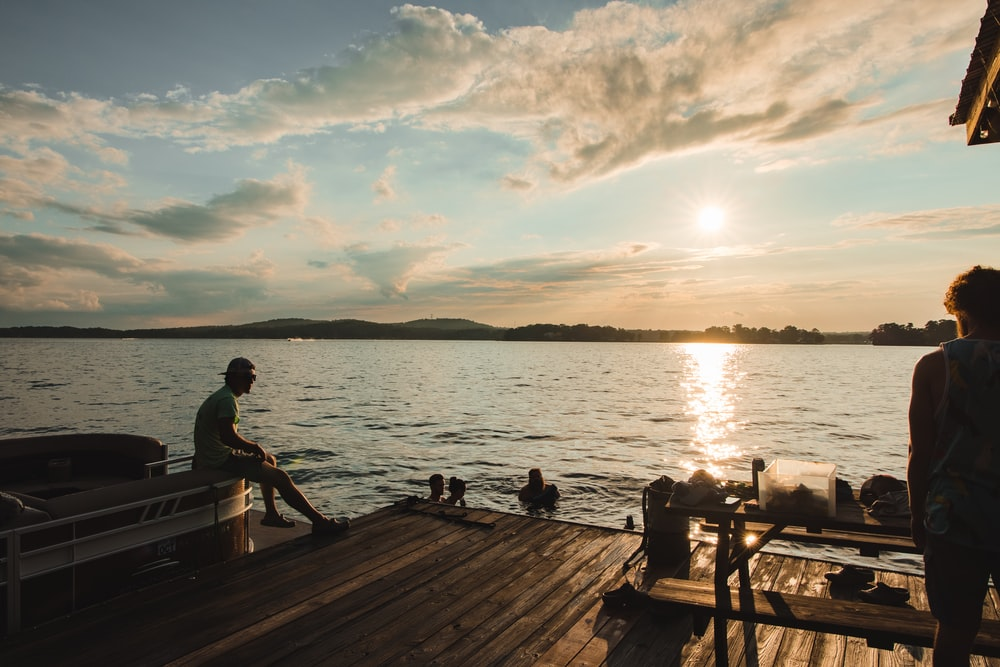 man and woman sitting on brown wooden dock during sunset