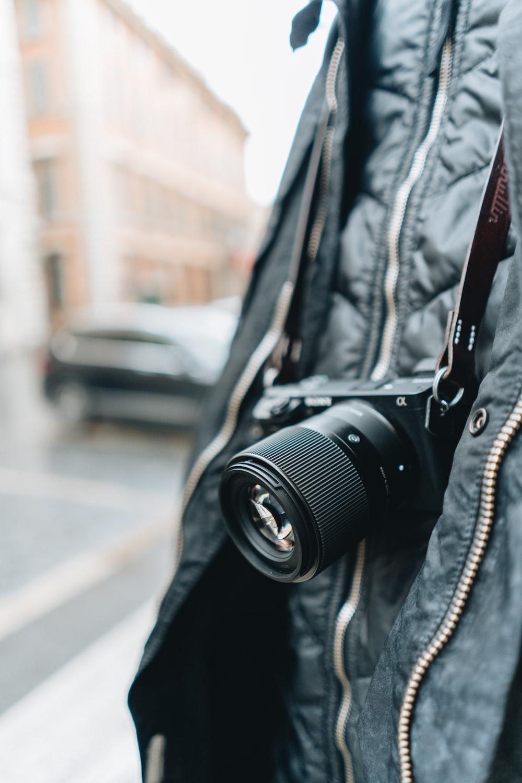 black dslr camera on black leather jacket