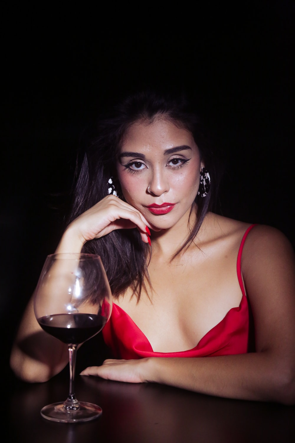 woman in red spaghetti strap top holding wine glass