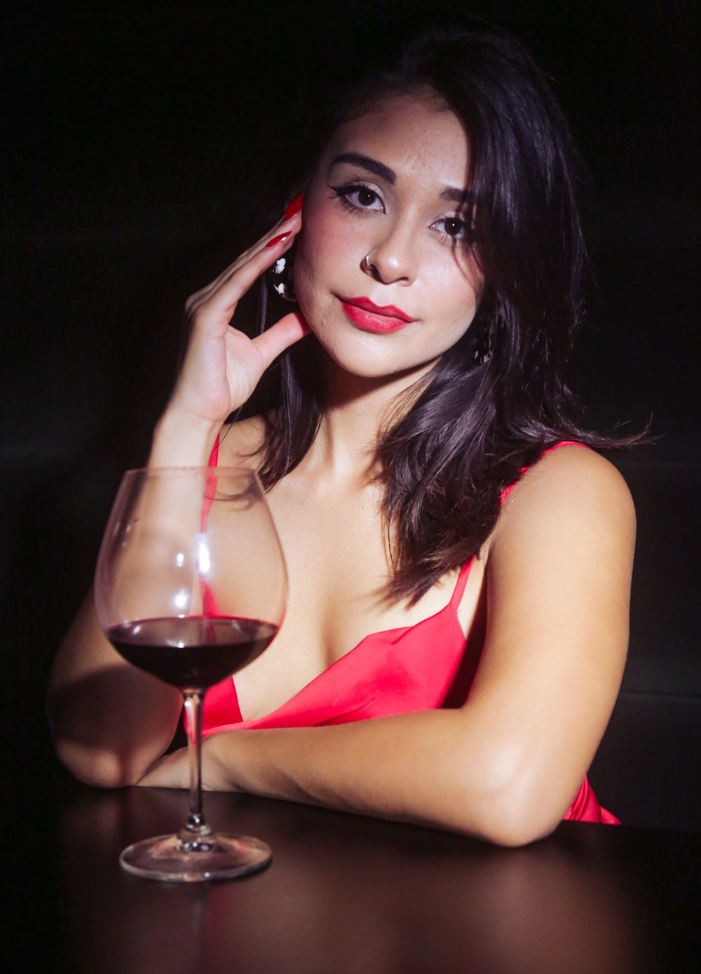 woman in red tank top holding wine glass