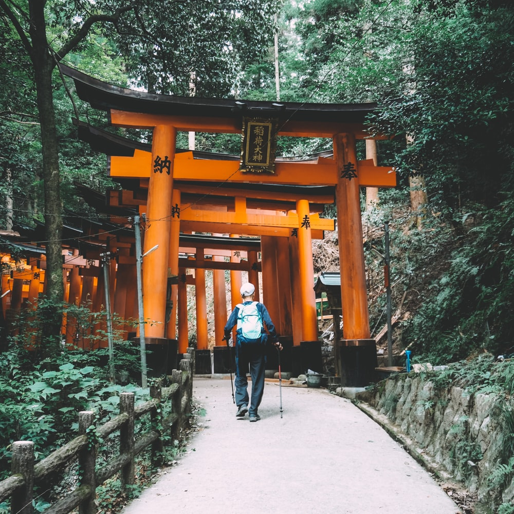 man in black jacket and black pants walking on pathway near brown wooden arch during daytime