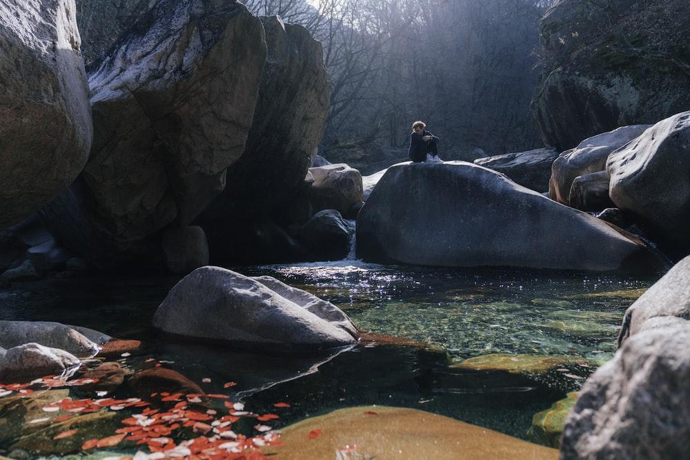 man in black jacket sitting on rock near river during daytime