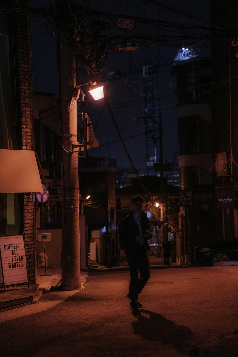 man in black jacket and pants walking on street during night time