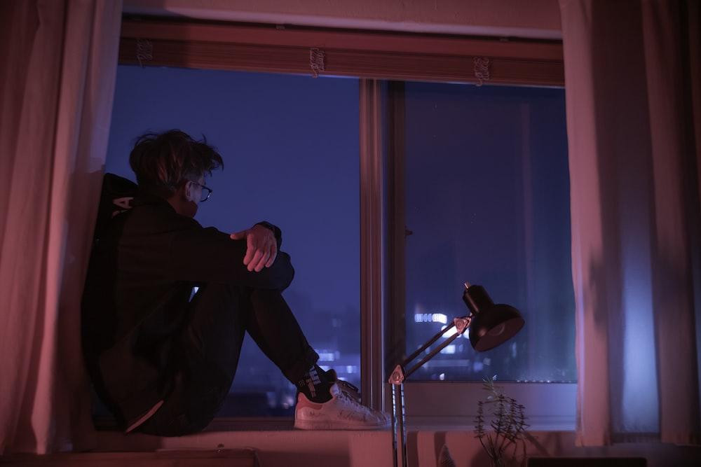 woman in black jacket sitting on window