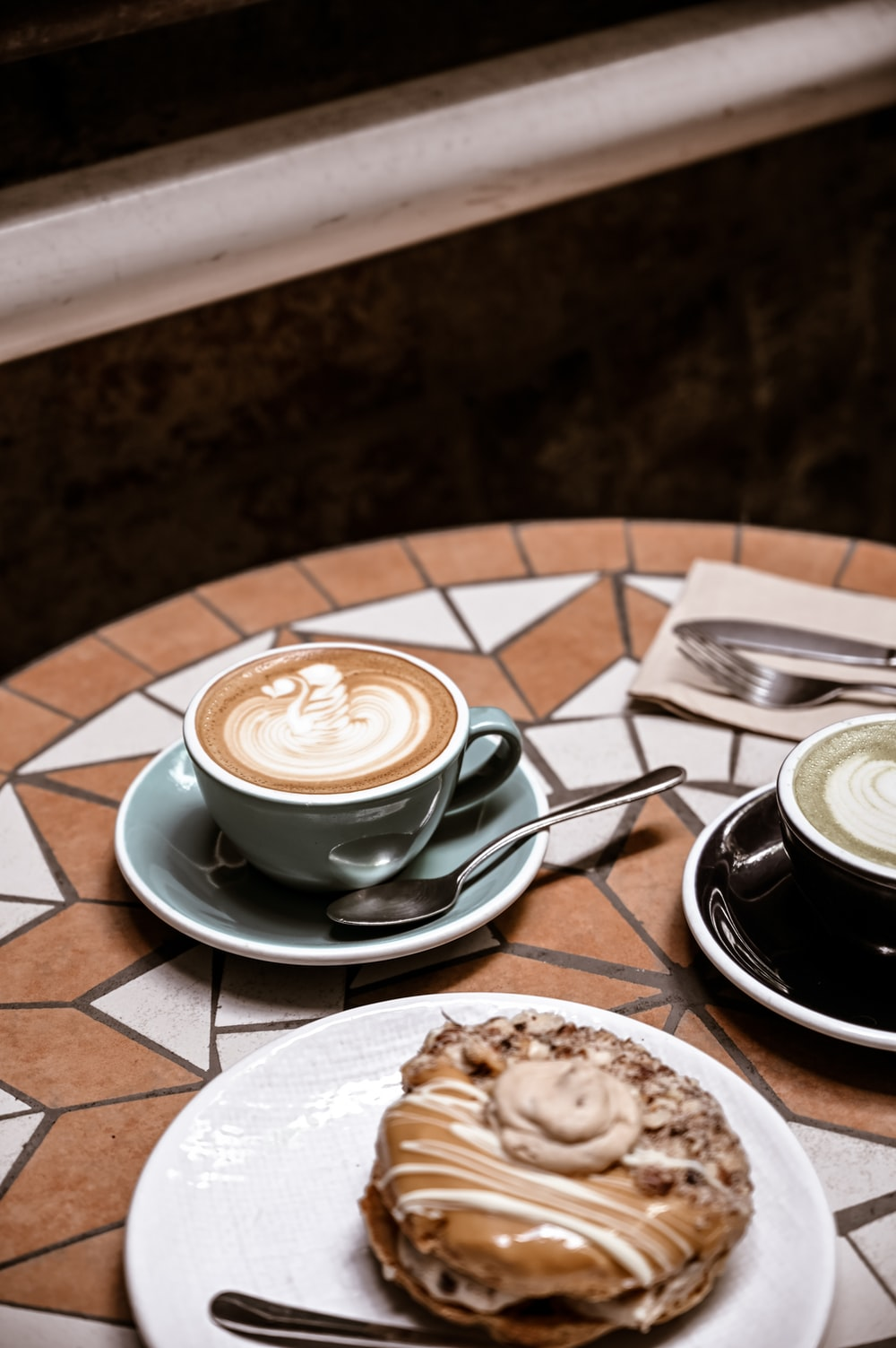 cappuccino in white ceramic cup on saucer beside stainless steel spoon on table