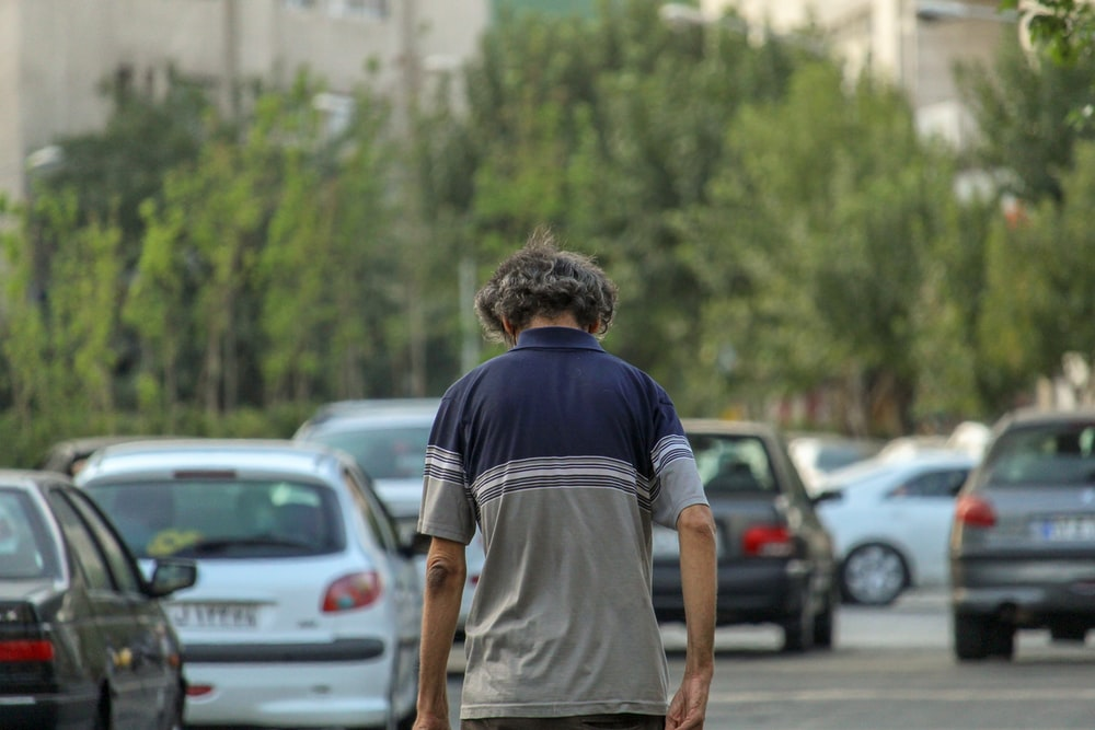 man in black t-shirt and brown shorts standing near cars during daytime