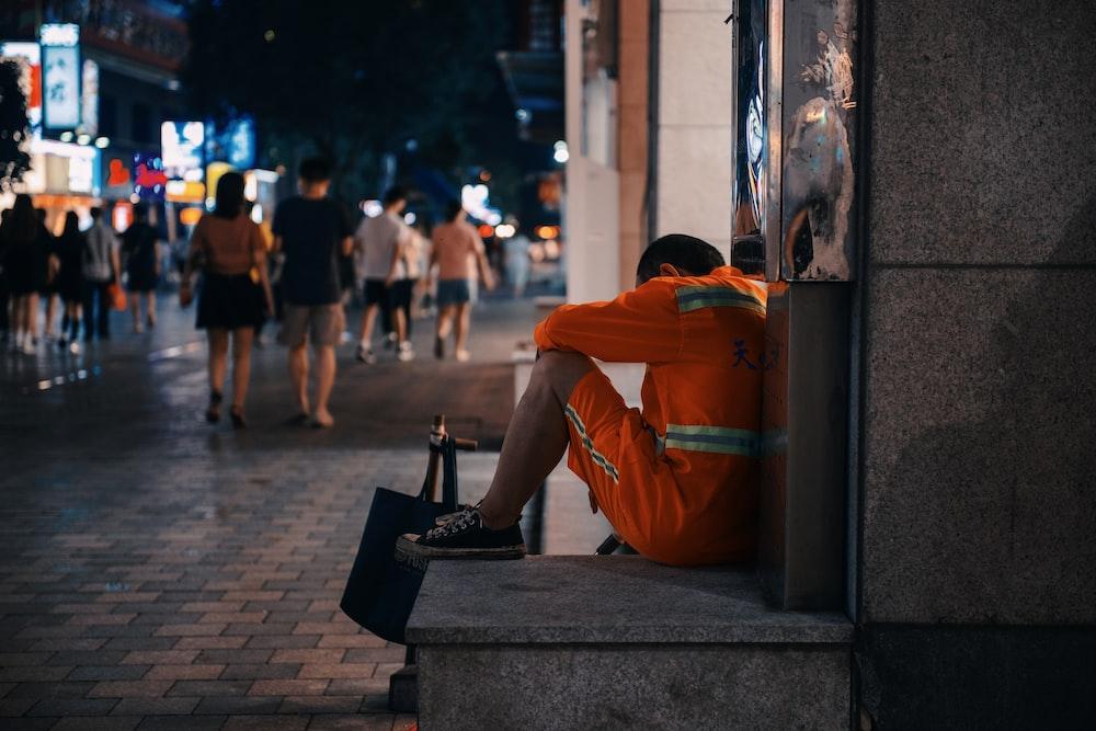 man in orange hoodie sitting on concrete bench