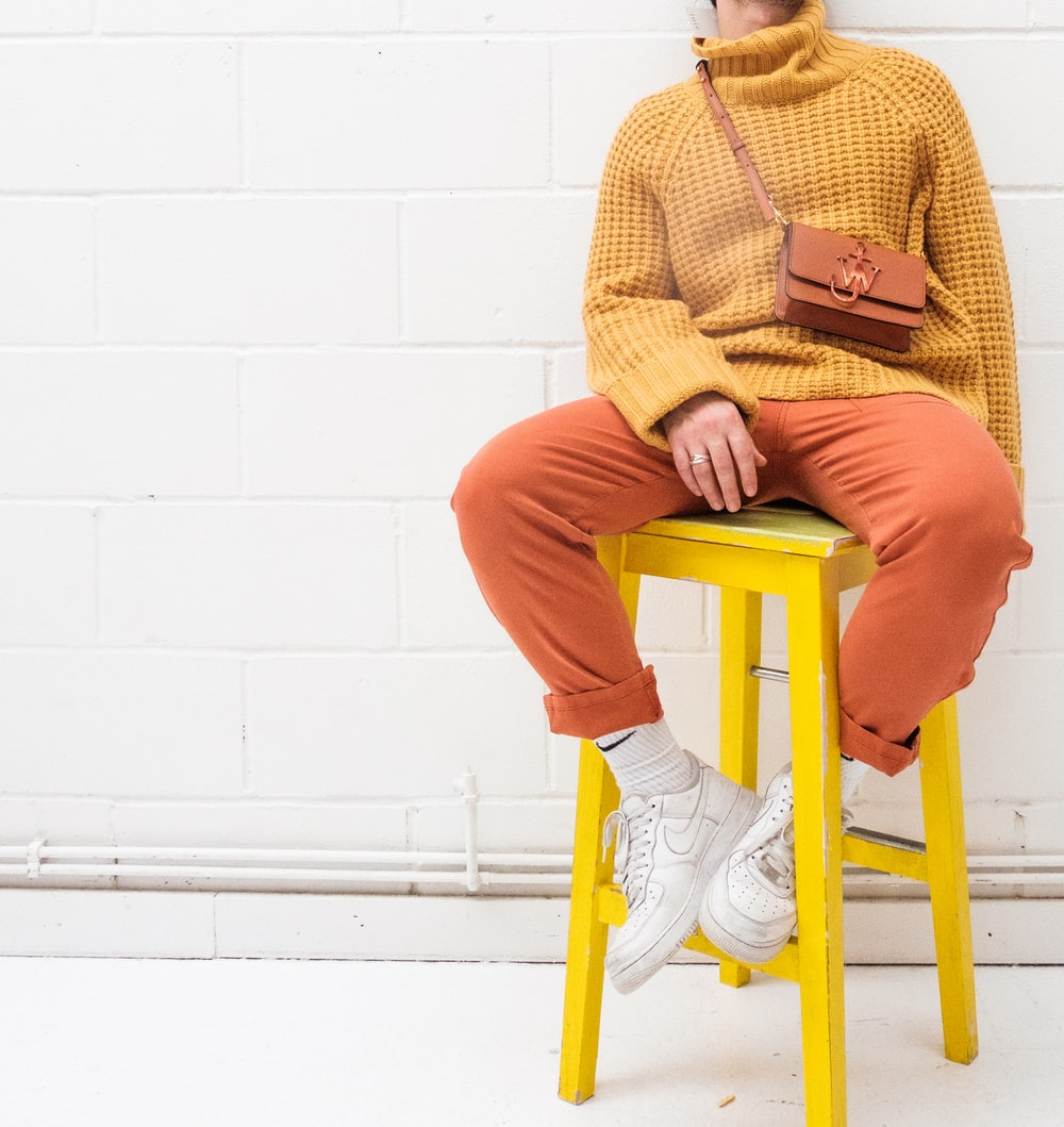 man in brown sweater and orange pants sitting on yellow plastic chair