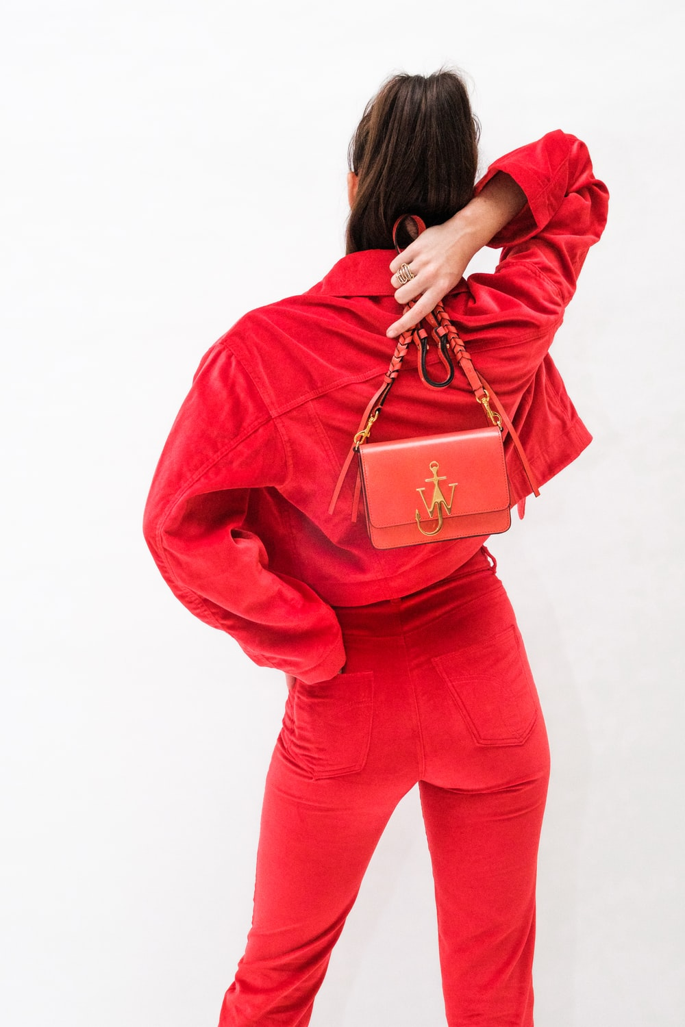 woman in red long sleeve shirt and red pants carrying brown leather handbag