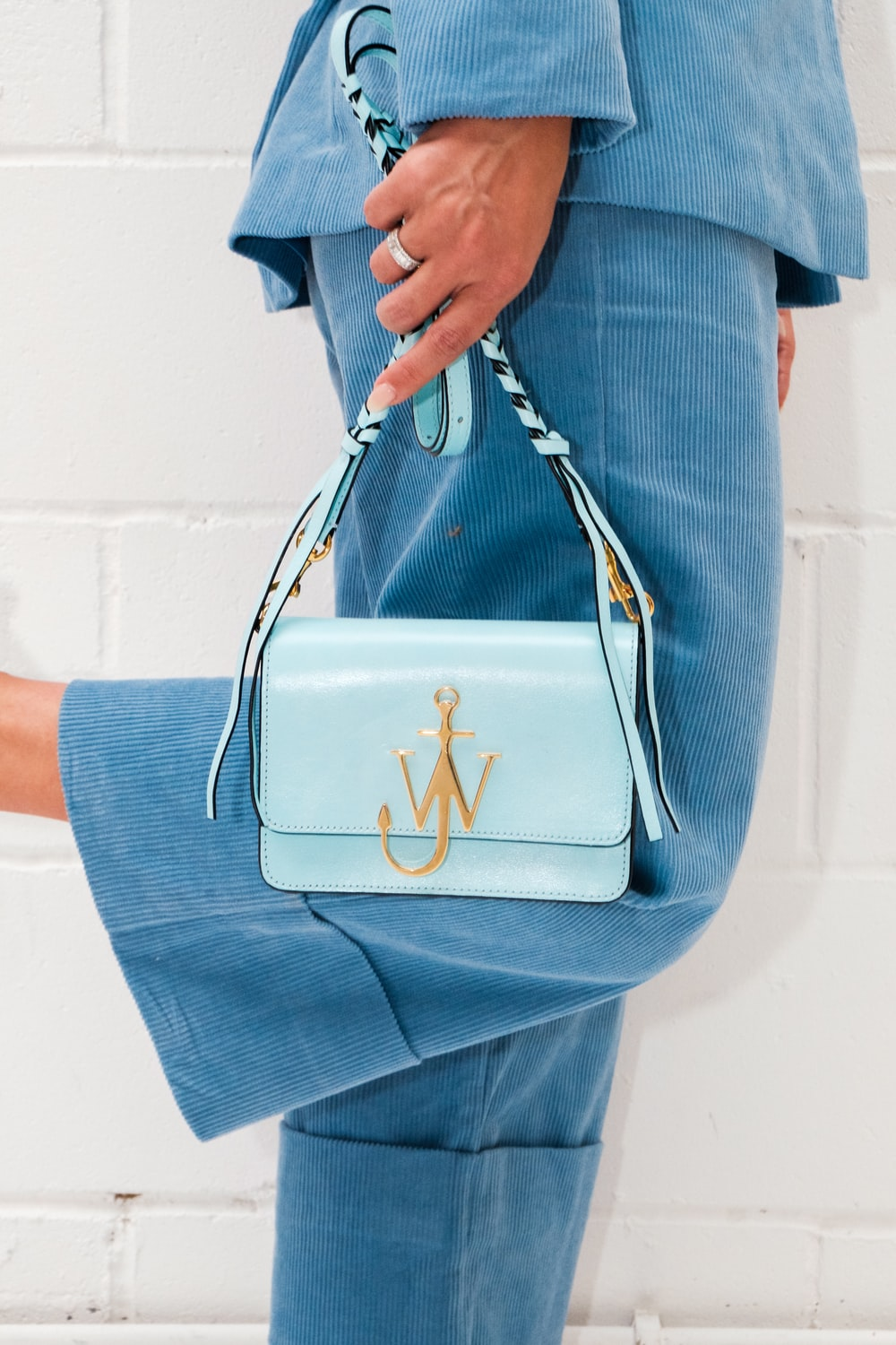 person in blue denim jeans holding white leather handbag