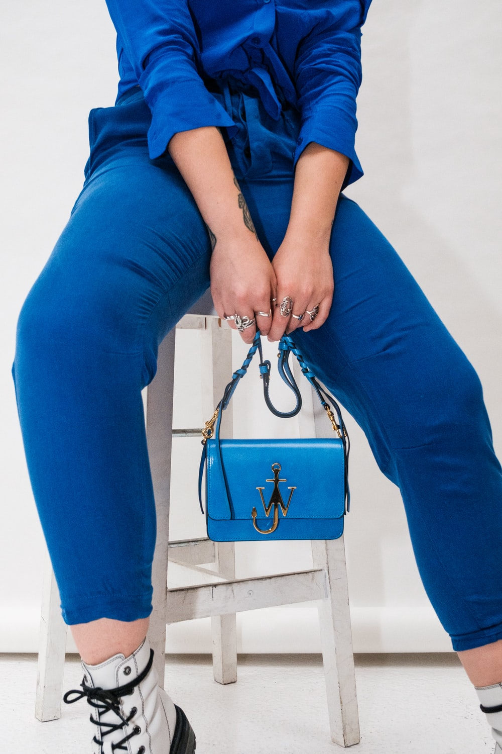 person in blue pants sitting on white wooden bench