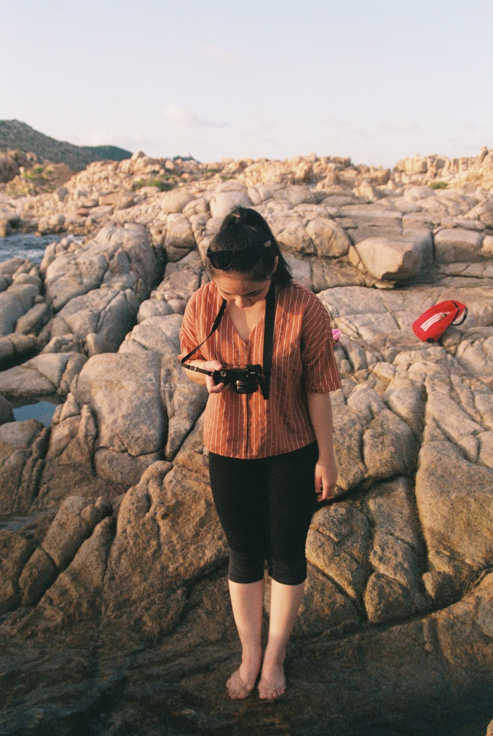 woman in black skirt standing on rocky shore during daytime