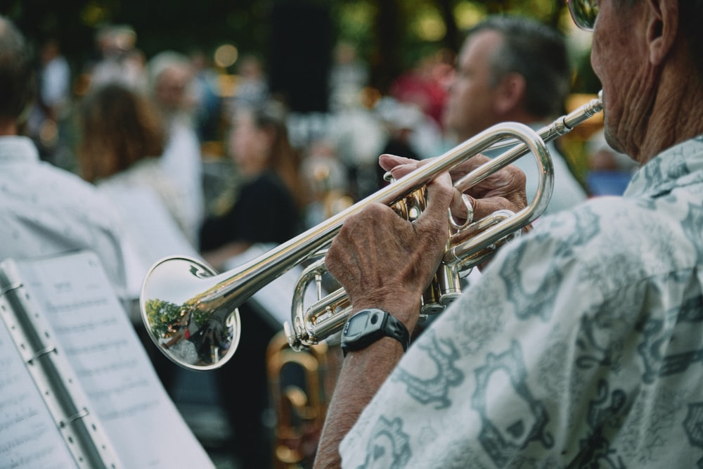 man in white and black floral shirt playing trumpet