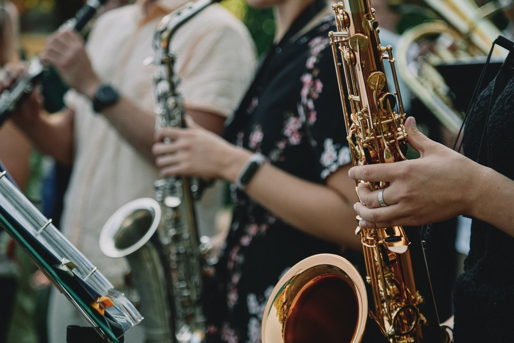person in black and white floral shirt playing saxophone