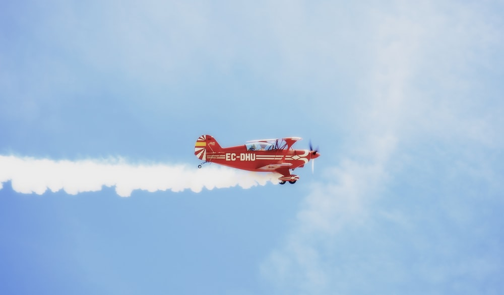 red and white jet plane in mid air during daytime
