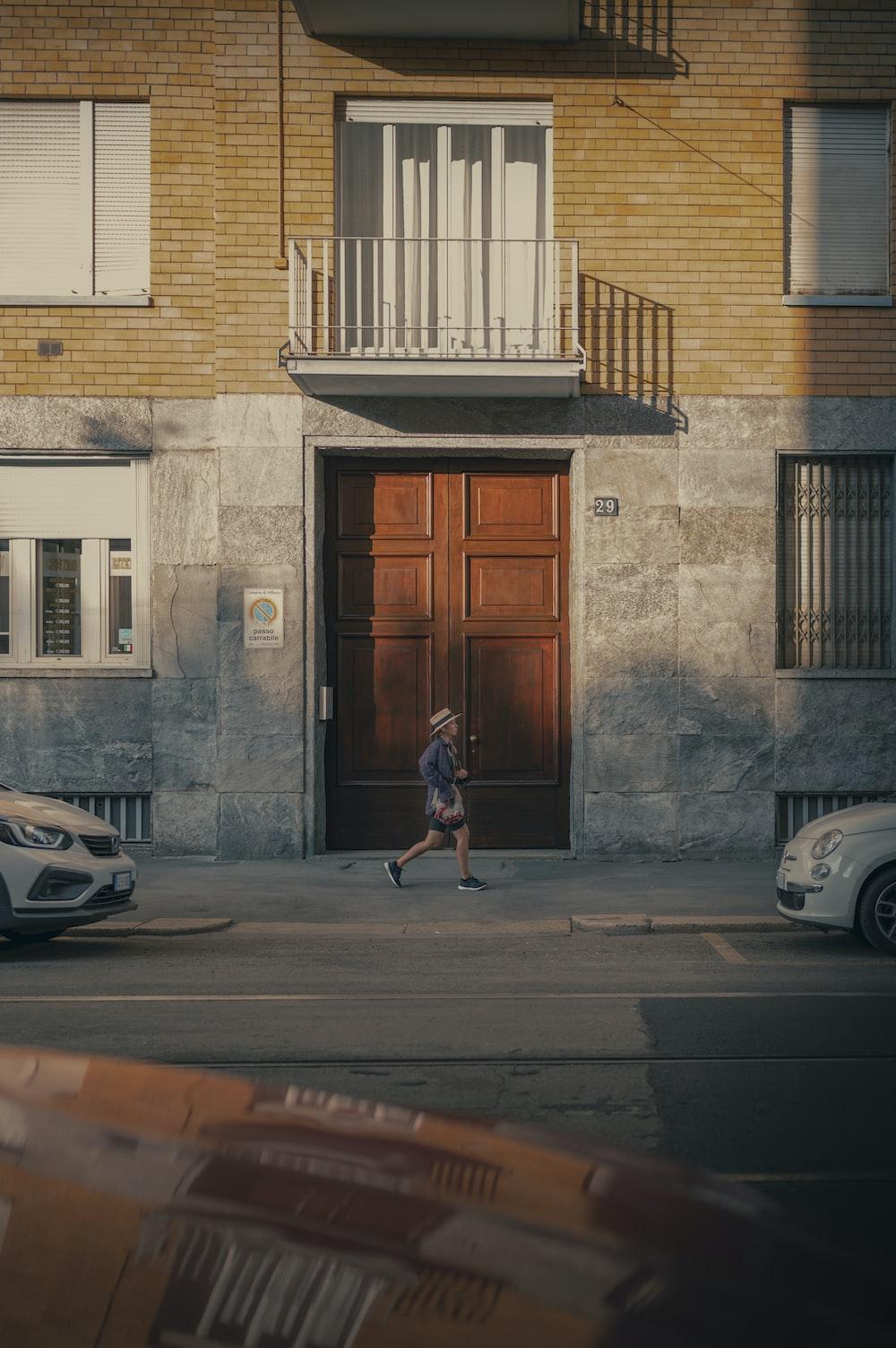 woman in red dress walking on sidewalk near brown wooden door during daytime