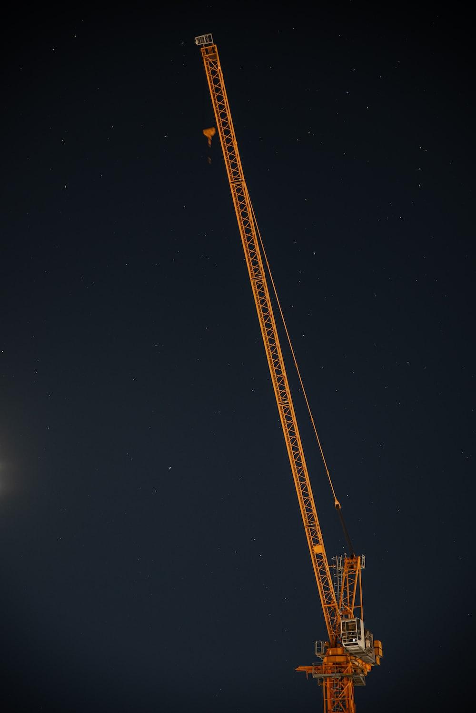 yellow and black crane under starry night