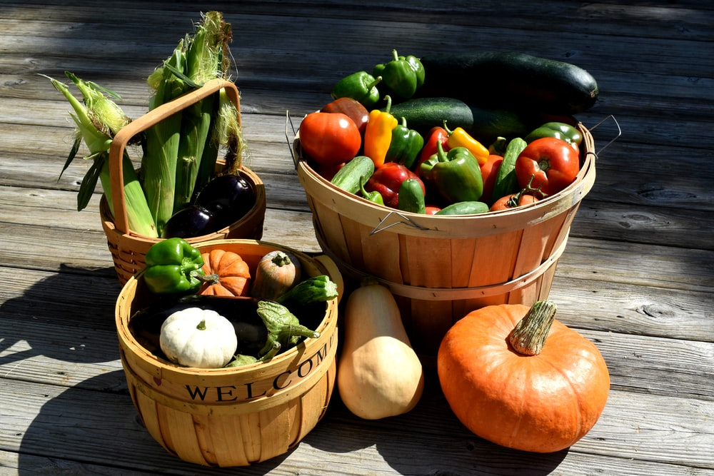 red and green bell peppers in brown wooden bucket